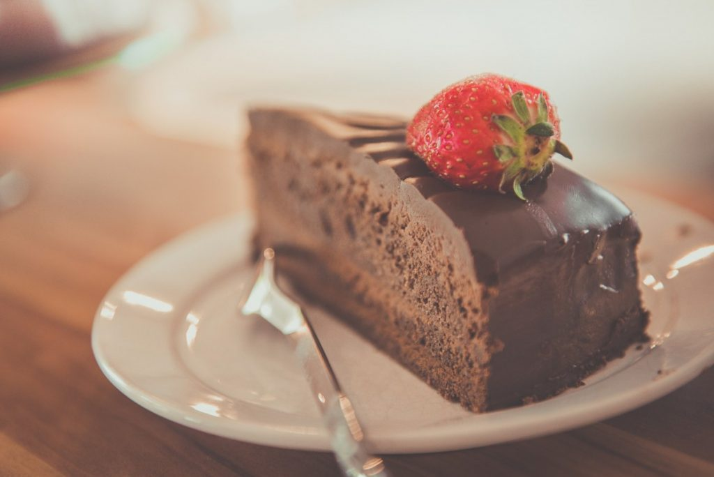 Super decadent indulgent rich slice of chocolate cake on a plate with a fork.