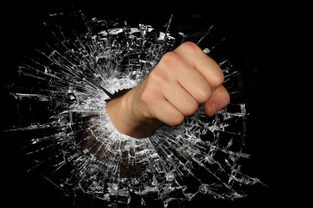Fist punching through glass with concentrated precision.